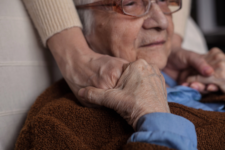 elderly woman holding someone's hand