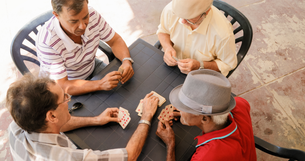 Group of Senior Men Playing Cards Game in Patio