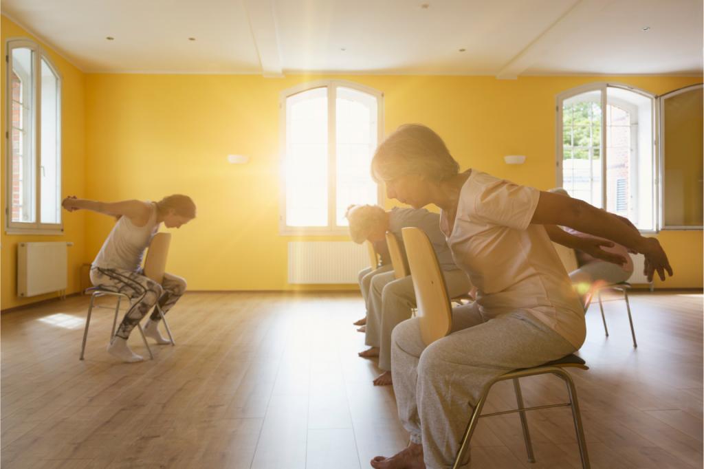 Teacher and active senior women doing yoga class on chairs